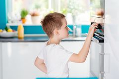 Child regulating temperature of the oven . Boy helping in the kitchen. Baking with children Royalty Free Stock Image