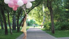 The child rejoices, having fun and fooling around. little girl with balloons in summer park. Children run through the park with a huge bunch of colorful balloons stock video footage
