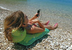 Child relax on beach. Young girl with sunglasses relaxing at Adriatic sea with cellular listen music on pebbles beach. Horizontal photo Royalty Free Stock Photography