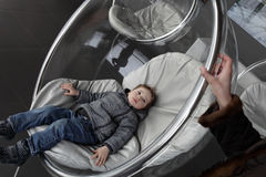 Child relaxes in glass chair Royalty Free Stock Images