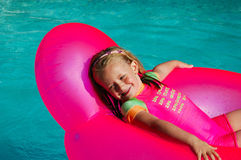 Child relaxing. A cute little caucasian blond girl child relaxing on a gum seat in the swimming pool outdoors in summertime and looking back to the water stock photography