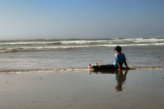 Child relaxing on beach. Rear view of young child sat on sandy beach at waters edge with waves in background royalty free stock image