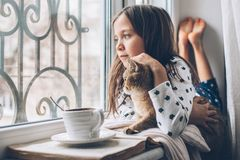 Child relaxing with a cat on a window sill stock images