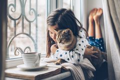 Child relaxing with a cat on a window sill stock photos