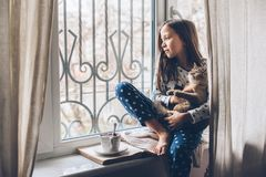 Child relaxing with a cat on a window sill. Child in pajamas relaxing on a window sill with pet. Lazy weekend with cat at home. Cozy scene, hygge concept royalty free stock photography
