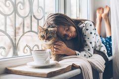 Child relaxing with a cat on a window sill. Child in pajamas relaxing on a window sill with pet. Lazy weekend with cat at home. Cozy scene, hygge concept stock images