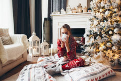 Child relaxing by Christmas tree at home Stock Photography
