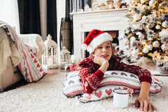 Child relaxing by Christmas tree at home Royalty Free Stock Images