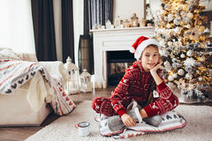 Child relaxing by Christmas tree at home Stock Image