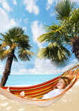 Child relaxing in a hammock royalty free stock photography