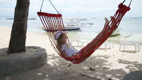 Child relaxing in a hammock on the sea beach stock video footage