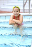 Child relaxing by swimming pool. Cute child with goggles relaxing by swimming pool Stock Photos