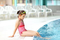 Child relaxing by swimming pool. Cute child with goggles relaxing by swimming pool Stock Photo