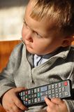 Child with remote control. Young child holding a remote control and looking forward Stock Photo