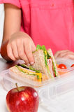 Child removing wholemeal sandwich out of lunchbox Royalty Free Stock Photos