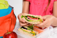 Child removing wholemeal sandwich out of lunchbox Stock Photos