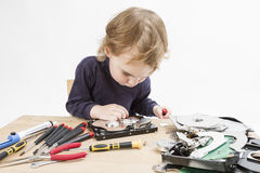 Child repairing hard disk drive. Young child repairing open hard disk drive with different tools Royalty Free Stock Photo