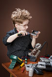 Child repairs digital cameras. Portrait of the boy in the studio, repairing the camera Royalty Free Stock Photo