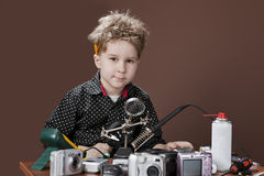 Child repairs digital cameras Royalty Free Stock Photography