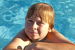 Child rest on his elbow at the edge of the pool Stock Image