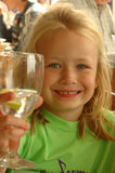Child in restaurant. A beautiful little blond girl child head portrait with happy expression in her caucasian face holding a glass of water in her white hand Royalty Free Stock Images