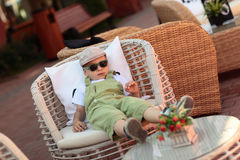 Child resting in armchair Stock Photos