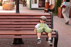Child resting on a bench Stock Photo