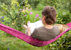 A child resting in  hammock. And reading a book  in garden Royalty Free Stock Photos