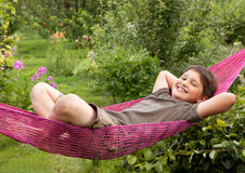A  child resting in  hammock. A happy child resting in red hammock in garden in summer sunny day Royalty Free Stock Images
