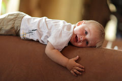 Child rests on back of sofa Royalty Free Stock Image