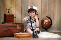 A child in a retro interior and an old phone sits on the floor. A small child a traveler in vintage decorations. Child traveler is calling by phone.r royalty free stock photography