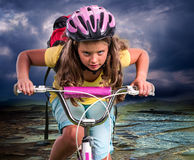 Child ride hard on bike to mountain Royalty Free Stock Image