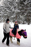 Child ride a pony in winter park with mom. Child ride a pony in winter park with mother Royalty Free Stock Photos