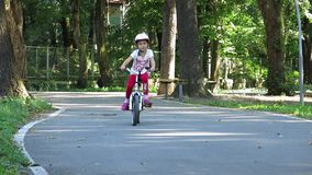 Child rides by bicycle. Cycling in the Park stock video