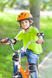 Child rides bike. Outdoors dressed in a colourful safety helmet and fleece green jacket royalty free stock image