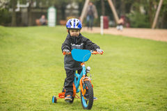 Child rides bike. Child rides a bike with training wheels in the park Stock Photo