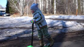 The child rides a scooter in the Park in early spring. Melting snow, snow and puddles on asphalt. Outdoor sports. A child rides his scooter in the Park stock video footage