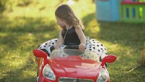 Child rides a red car