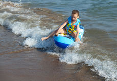 Child rides a wave of the sea. Stock Image