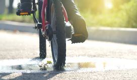The child is riding a bicycle close-up passing through a puddle and splashing water in the rays of the setting sun in the autumn d. Ay stock photography
