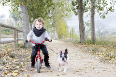 Child riding bike with dog Royalty Free Stock Images