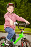 Child riding bike with safety helmet Stock Images