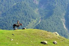 Child riding horse in Sonamarg, Kashmir, India. Child riding a brown horse in the green meadows of Sonamarg, Kashmir with mountains in the background. Sonamarg stock images