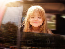 Child Riding in Car Looking Out Window. A little girl is sticking her head out the car window and looking down for a road trip or travel concept stock photos