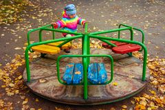 Child is riding carousel in children`s playground in autumn. Little girl playing. Stock Images
