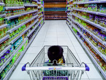 Child riding a grocery cart in a grocery Stock Photos