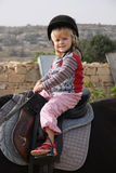 Child riding a horse. Close up of 3 year old girl riding a horse Stock Photos