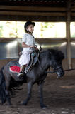 Child riding a pony. Little girl  riding a pony horse Royalty Free Stock Photo
