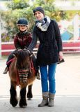 Child riding on a pony. Mother riding her son on a pony wearing protective helmet Royalty Free Stock Images