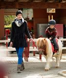 Child riding on a pony. Mother riding her son on a pony wearing protective helmet Royalty Free Stock Photos